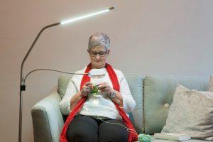 dame aan het breien met daylight lamp en loep